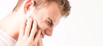 Tandvärk medicin, hälsovårdbegreppet, tandproblem, lidande för den unga mannen från tanden smärtar, karies, i en vit t-skjorta på royaltyfri bild