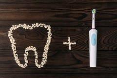Tandzorg met een elektrische borstel Tanden en elektrische borstel op houten achtergrond Correcte tanden Mondelinge hygi?ne Metaa stock foto