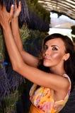 Taned-Frau, die einen Lavendelblumenstrauß erreicht. Lizenzfreies Stockbild