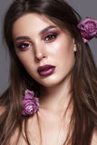 Taned young model with professional makeup and withered roses in hair royalty free stock images