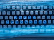 Tangentbordet med glad jul för text på knappar som täckas med snö exponerad av blått neonljus med ljust, spårar arkivfoton