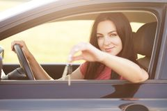Tangenten för bilägarehåll, sitter på chaufförplatsen, uppehällehand på hjulet, annonserar eller säljer bilen Den härliga brunett royaltyfria bilder