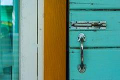 Tangenten för metall för dörrlåset är en blå bakgrund Royaltyfri Foto