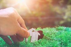 Tangenten i hand och huset modellerar, planerar besparingpengar av mynt arkivbild