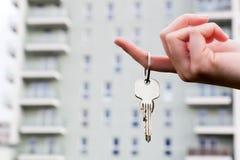 Tangenter för ett fastighetsmäklareinnehav till en ny lägenhet i henne händer. Royaltyfria Foton