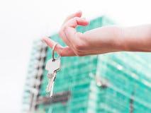 Tangenter för ett fastighetsmäklareinnehav till ett nytt hus i henne händer. Arkivbilder