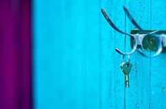 Tangenter som utanför hänger från en krok på den gamla målade träväggen Arkivfoto