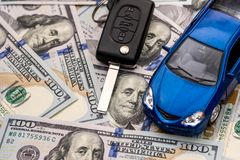 Tangenter till bilen och bilen som ligger på 100 dollar Arkivbild