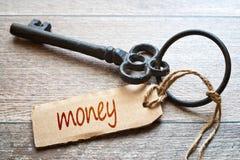 Tangenter till pengar - begreppsfoto Tangenter till pengar - begreppsfoto Gammal tangent med den pappers- etiketten på trägammal  Arkivfoton