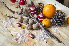 Tangerin, apelsiner, nutsmed kottar och leksaker på bräden Arkivfoto