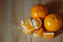 Tangerin som skalas på en trätabell royaltyfria bilder
