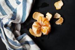A tangerina descascada encontra-se na placa Imagem de Stock