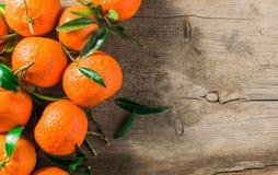 Tangerinapelsiner, mandariner, clementines, citrusfrukter med sidor i korg över lantlig träbakgrund, kopieringsutrymme arkivbild