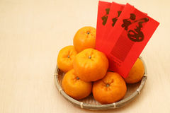 Tangerinas chinesas na cesta com os pacotes vermelhos chineses do ano novo - série 2 Fotografia de Stock Royalty Free