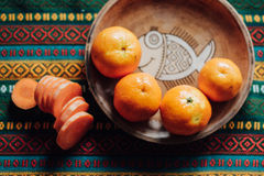 Tangerinas e cenoura em uma placa de terra em uma toalha de mesa brilhante Imagens de Stock