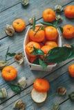 Tangerinas e frutos maduros dos fezalis com folhas e galhos em uma tabela de madeira velha A vista da parte superior fotos de stock royalty free