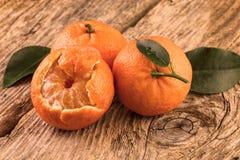 Tangerinas três frutos no fundo de madeira A vida do vintage ainda tonificou a imagem Imagem de Stock