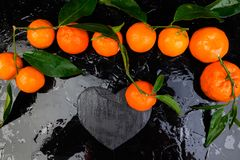 Tangerine γύρω τη μαύρη καρδιά πλακών που διαμορφώνεται με Στοκ φωτογραφία με δικαίωμα ελεύθερης χρήσης