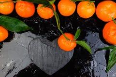 Tangerine γύρω τη μαύρη καρδιά πλακών που διαμορφώνεται με Στοκ Εικόνες