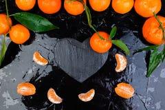 Tangerine γύρω τη μαύρη καρδιά πλακών που διαμορφώνεται με Στοκ εικόνα με δικαίωμα ελεύθερης χρήσης