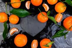 Tangerine γύρω τη μαύρη καρδιά πλακών που διαμορφώνεται με Στοκ φωτογραφίες με δικαίωμα ελεύθερης χρήσης