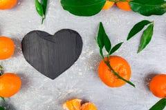 Tangerine γύρω τη μαύρη καρδιά πλακών που διαμορφώνεται με Στοκ εικόνες με δικαίωμα ελεύθερης χρήσης