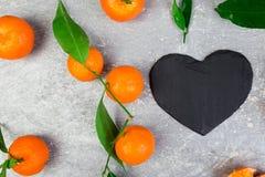 Tangerine γύρω τη μαύρη καρδιά πλακών που διαμορφώνεται με Στοκ Φωτογραφία