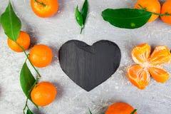 Tangerine γύρω τη μαύρη καρδιά πλακών που διαμορφώνεται με Στοκ Εικόνα