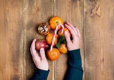 Tangerine παιχνιδιών Χριστουγέννων εσπεριδοειδών εκμετάλλευσης χεριών γυναικών Χριστουγέννων καραμελών καλάμων το ξύλινο επίπεδο  Στοκ φωτογραφία με δικαίωμα ελεύθερης χρήσης