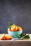 Tangerine φρούτα με τα πράσινα φύλλα στον ξύλινο πίνακα Στοκ Φωτογραφία