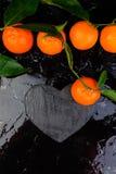 Tangerine вокруг при черное сформированное сердце шифера Стоковая Фотография RF