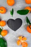Tangerine вокруг при черное сформированное сердце шифера Стоковые Изображения