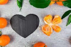 Tangerine вокруг при черное сформированное сердце шифера Стоковое Фото