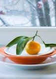 Tangerine с ветвью и листьями на плите на фоне окна снег Стоковые Изображения RF