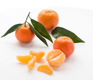 Tangerine. Fresh tangerine fruits  with green leaves and segments isolated on white background Royalty Free Stock Images