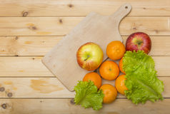 Tangerine, apples and salad leaves with wooden cutting plate on a wooden background Royalty Free Stock Photos