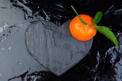 Tangerine around with black slate heart shaped. Stock Photo