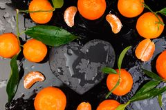 Tangerine around with black slate heart shaped. Royalty Free Stock Photo