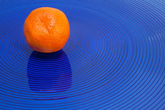 Tangerine on blue Royalty Free Stock Photos
