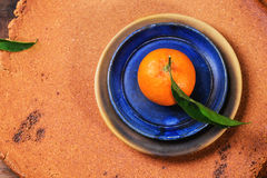 Tangerine on blue plate Royalty Free Stock Photos
