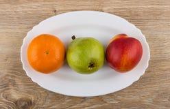 Tangerine, bonkreta i nektaryna w owalnym naczyniu na drewnianym stole, Zdjęcie Stock