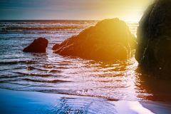 Sun setting behind rock formations in shallow water at the beach stock images