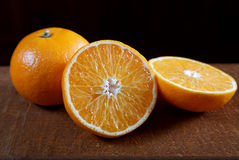 Tangerine cut on an old table. Closeup royalty free stock image