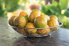 Tangerine in einem silbernen Metallkorb auf dem alten hölzernen stockfotografie