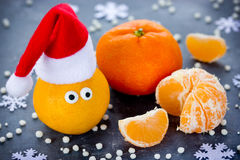 Tangerine with eyes in Santa hat, Christmas Xmas New Year concep Royalty Free Stock Photography