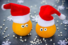 Tangerine with eyes in Santa hat Christmas Xmas New Year concept Stock Photos
