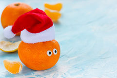 Tangerine with eyes in Santa hat Christmas Xmas New Year concept Royalty Free Stock Photography
