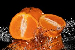 Tangerine falling into water on black mirror Royalty Free Stock Images