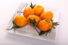 Fresh some tangerine on dish. Tangerine fruits on white background Royalty Free Stock Photo