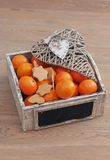 Tangerine and gingebread. Box of mandarins and with decorative heart royalty free stock image